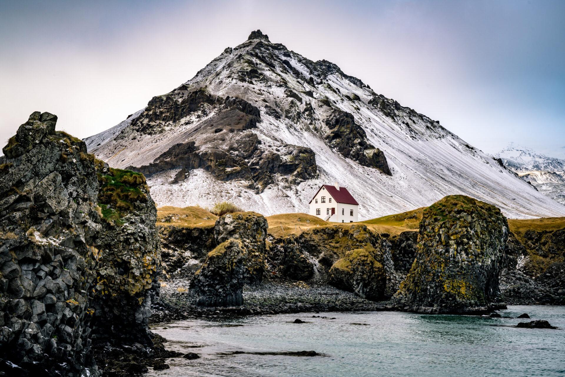 Contrast van sneeuw en lava in Arnarstapi